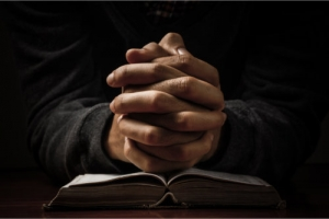 praying hands on top of the holy bible